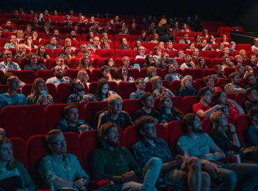 An image of people sitting in a full cinema