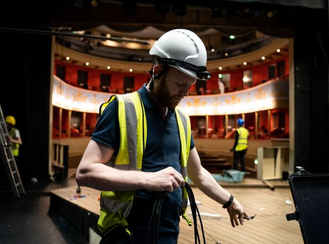 A LAMDA technical student on the stage of The Sainsbury Theatre during his training