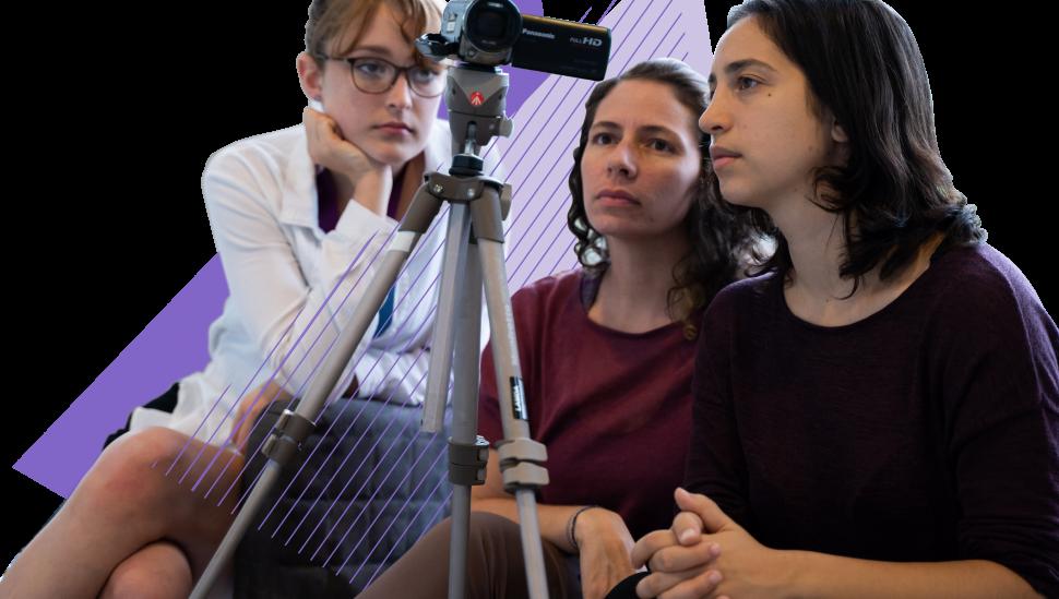 Three LAMDA Short course students looking at a camcorder