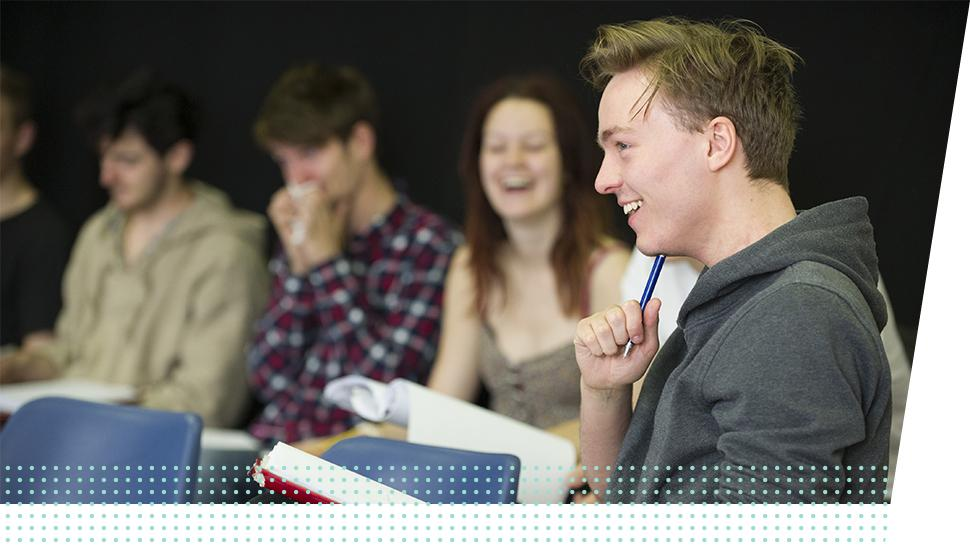 A LAMDA learner laughs holding a script